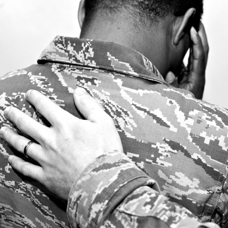 A U.S. Air Force Airman places his hand on another Airman's back at Shaw Air Force Base, S.C., November 21, 2014, photo by Senior Airman Tabatha Zarrella/U.S. Air Force