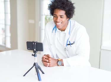 Doctor using a smartphone on a tripod for a video call, photo by AaronAmat/Getty Images