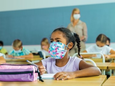 A tween girl wearing a protective mask at her desk in a classroom, photo by JackF/Adobe Stock