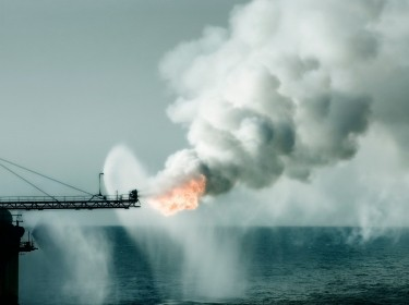 An ocean gas rig emits plumes of smoke