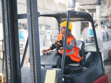 A woman wearing a hard had and hi-viz vest and driving a forklift