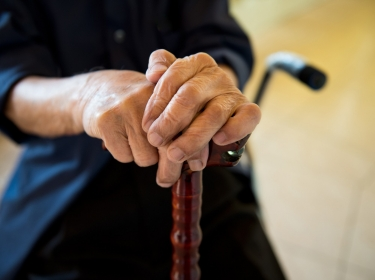 elderly person's hands on walking cane