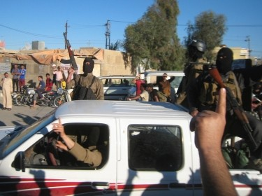 Al Qaeda fighters celebrate on vehicles taken from Iraqi security forces in Fallujah, March 20, 2014