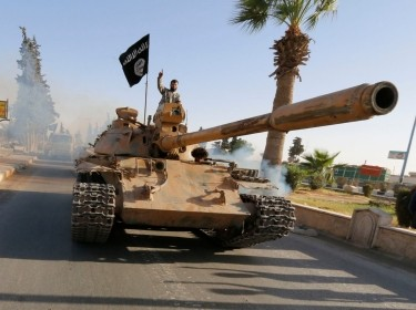 Militant Islamist fighters on a tank take part in a military parade along the streets of northern Raqqa province, Syria, June 30, 2014