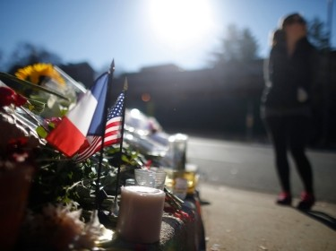 A passerby pauses near a makeshift memorial with U.S. and French flags outside the French embassy in Washington, November 16, 2015