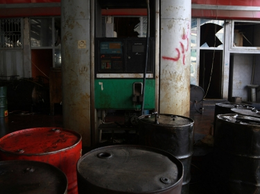 Barrels of fuel are displayed inside a damaged, non-functioning petrol station in Aleppo, Syria, January 13, 2015