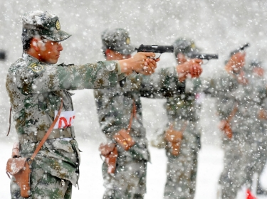 Chinese People's Liberation Army (PLA) soldiers practice shooting with pistols at a military base amid heavy snowfalls in Hami, Xinjiang Uighur Autonomous Region May 23, 2014