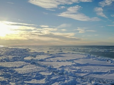 Aerial view of the horizon and sea ice at the ice floe edge at midnight, Baffin Island, Canada