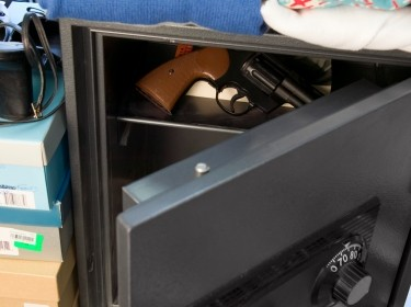 Gun inside open safe, photo by Creatas/Getty Images