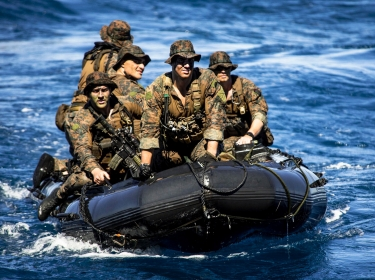 Marines approach the well deck of the amphibious assault ship USS Bonhomme Richard in a combat rubber raiding craft following a simulated boat assault to support a certification exercise in the Coral Sea, Aug. 8, 2013