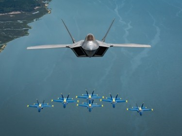 Maj. Paul Lopez, F-22 Demonstration Team commander, flies above the U.S. Navy Blue Angels' iconic diamond formation over Beaufort, S.C., April 25, 2019. The historic flight featured two of the world's premier aerial demonstration teams side-by-side for the first time ever. (U.S. Air Force photo by 2nd Lt. Samuel Eckholm)