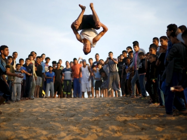 A Palestinian youth demonstrates his parkour skills at Shati refugee camp in Gaza City, November 27, 2015