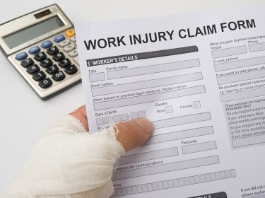 Bandaged hand holding a work injury claim form