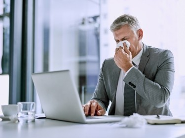 Businessman holding a tissue over his nose while looking at his laptop