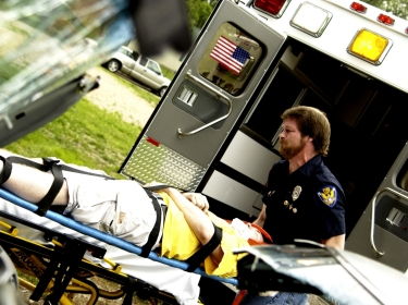 An EMT loading a patient into an ambulance